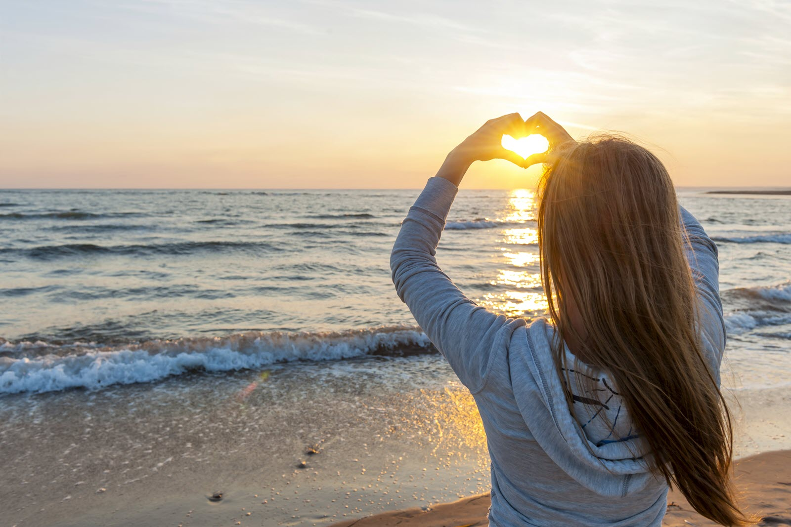 Woman making heart with hands at sunset